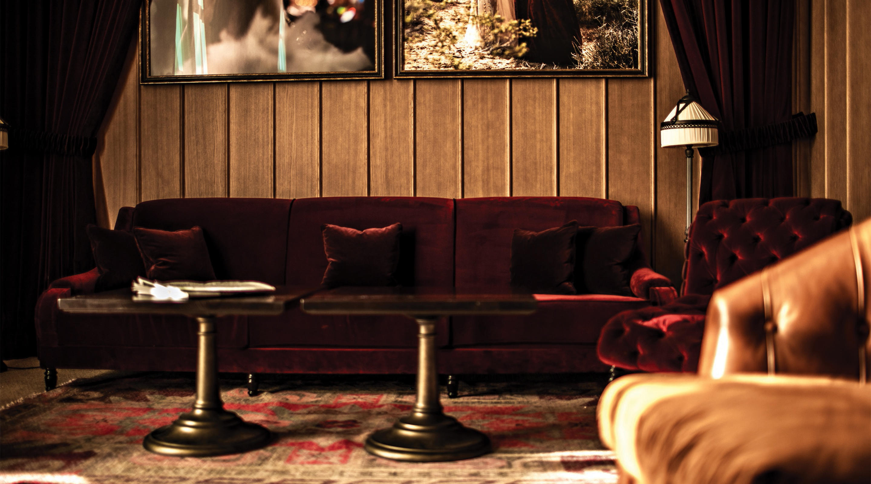 A red velvet couch inside NoMad Bar.